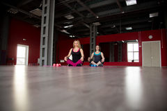 Two pretty girls sit cross-legged on mats in fitness center. Two pretty girls sit cross-legged in lotus pose on mats in sports hall Stock Photos