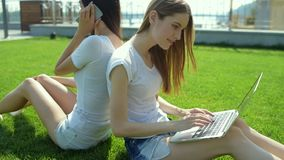 Two pretty girls sitting back to each other on the grass. Modern communication. Two pretty young girls sitting back to each other on the grass while speaking on stock video footage