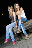 Two pretty girls sitting on a stone Stock Photo