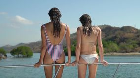 Two pretty girls stand out of boat handrailing and dive together into water, girlfriends having fun on yacht in a bay stock footage