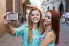 Two pretty girls taking selfie. Urban background. We love selfie Stock Photo