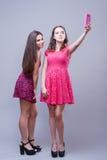 Two pretty girls taking selfies. Stock Photo