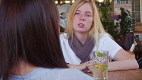 Two pretty girls talking and drinking coffee sitting in cafe.  stock video footage