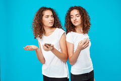Two pretty girls twins looking at phones over blue background. Stock Photography