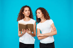 Two pretty girls twins reading book over blue background. Royalty Free Stock Image