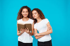 Two pretty girls twins smiling, reading book over blue background. Stock Image