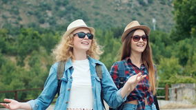 Two pretty girls young women friends travelers walk outdoors on mountain scene.  stock video footage