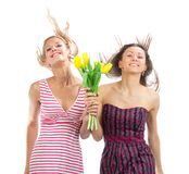 Two pretty happy girls with bouquet flowers. Two pretty happy girls with bouquet of tulips flowers walking smiling isolated on a white background Stock Image