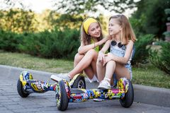 Two pretty happy girls resting with hoveboards. Happy girl riding on hover board or gyroscooter  and chatting outdoors at sunset in summer. Active life concept Stock Photography
