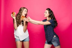 Two pretty and hungry girls wanting two big hamburger.