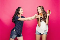 Two pretty and hungry girls wanting two big hamburger. royalty free stock image