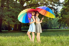 Two pretty ladies holding colorful umbrellas royalty free stock photo