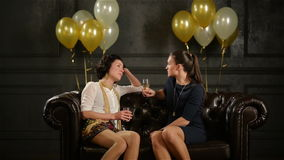 Two Pretty Lady are Siting on the Brown Sofa with Glasses of Champagne and Talking about Something Funny During a Party. Black Wall with Golden and White Air stock video