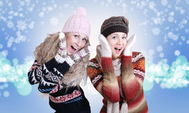 Two pretty laughing surprised girls. Two beautiful girls laughed in warm winter clothes over background with snowflakes Stock Photo