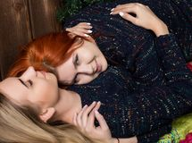 Two pretty lesbians girlfriends kissing and hugging in a cozy atmosphere.  Stock Photography