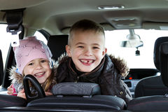 Two pretty little children boy and girl in a car interior Royalty Free Stock Image