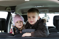 Two pretty little children boy and girl in a car interior Stock Photo