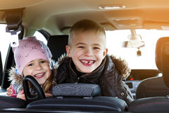 Two pretty little children boy and girl in a car interior, trave Royalty Free Stock Photo