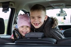 Two pretty little children boy and girl in a car interior Royalty Free Stock Images