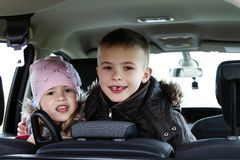 Two pretty little children boy and girl in a car interior Royalty Free Stock Photo