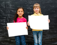 Two pretty little girls with blank paper in hands Stock Photos