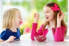 Two pretty little girls eating raspberries at home. Cute children enjoying their healthy fresh organic fruits and berries. Stock Photo