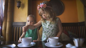 Two pretty little girls are having tea in a cafe. Happy childhood. Two pretty little girls are having tea in a cafe. Two littl blonde girls with the curly hair stock video