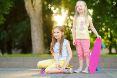 Two pretty little girls learning to skateboard on beautiful summer day in a park. Children enjoying skateboarding ride outdoors. Stock Images