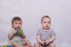 Two pretty little kids sitting with a toys in their hands. Funny girl and lovely baby boy on the grey background with toys Stock Photography