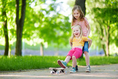 Two pretty little sisters having fun together learning to skateboard outdoors Stock Image