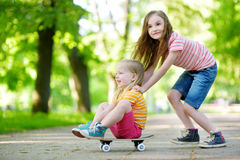 Two pretty little sisters having fun together learning to skateboard outdoors Stock Photos
