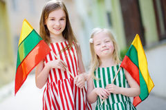 Two pretty little sisters holding tricolor Lithuanian flags Royalty Free Stock Photo