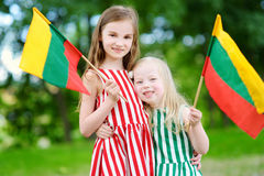 Two pretty little sisters holding tricolor Lithuanian flags Royalty Free Stock Photography
