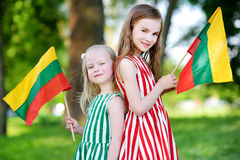 Two pretty little sisters holding tricolor Lithuanian flags Stock Photos