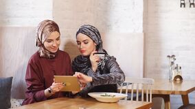 Two pretty muslim woman use tablet in cafe. Two pretty muslim woman use tablet in cafe stock video