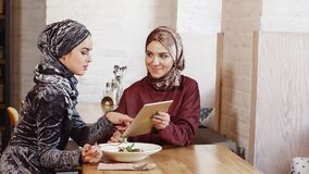 Two Pretty Muslim Woman Use Tablet in Cafe. Two Pretty Muslim Woman Use Tablet in Cafe stock video footage
