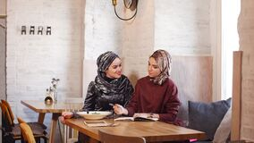 Two pretty muslim women with hijab in cafe. Sitting on couches at a table and talking. Two pretty muslim women with hijab in cafe. Sitting on couches at a table stock video footage