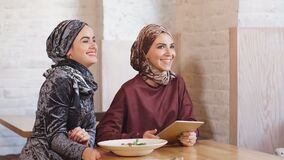 Two pretty muslim women with hijab in cafe. Sitting on couches at a table and talking. Two pretty muslim women with hijab in cafe. Sitting on couches at a table stock footage