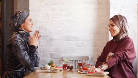 Two pretty muslim women with hijab in cafe. Sitting on couches at a table and talking. Two pretty muslim women with hijab in cafe. Sitting on couches at a table stock video