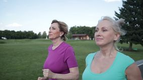 Two pretty senior females joggers training in park stock footage