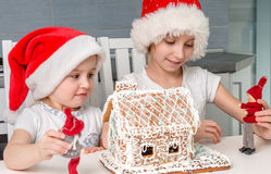 Two pretty sisters playing toys with biscuit house Royalty Free Stock Images