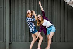 Two pretty smiling blond girls wearing checkered shirts, caps and denim shorts are balancing in front of the black wall stock photo