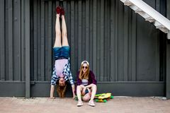 Two pretty smiling blond girls wearing checkered shirts, caps and denim shorts are balancing in front of the black wall royalty free stock images