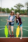 Two pretty smiling blond girls wearing checkered shirts, caps and denim shorts are standing on the sportsfield with stock image