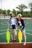 Two pretty smiling blond girls wearing checkered shirts, caps and denim shorts are standing on the sportsfield with stock images