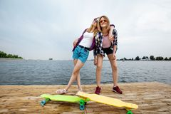 Two pretty smiling blond girls wearing checkered shirts and denim shorts are standing on the pier and having fun with stock image
