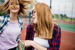 Two pretty smiling blond girls wearing checkered shirts are standing on the sportsfield and having fun. Sport and cool stock image