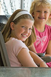 Two pretty, smiling little girls. Two pretty little girls seated at a table smile at the camera royalty free stock photography