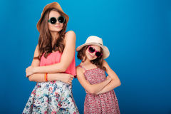 Two pretty smiling sisters standing and posing with hands folded Royalty Free Stock Photos