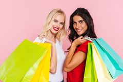 Two pretty smiling women holding packages on shoulders. And looking at the camera over pink background stock images